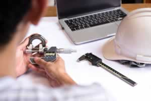 Engineer man hand measuring bearing with digimatic micrometer
