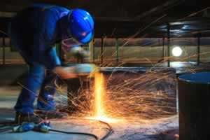 Male worker wearing protective clothing and repair grinding fabrication