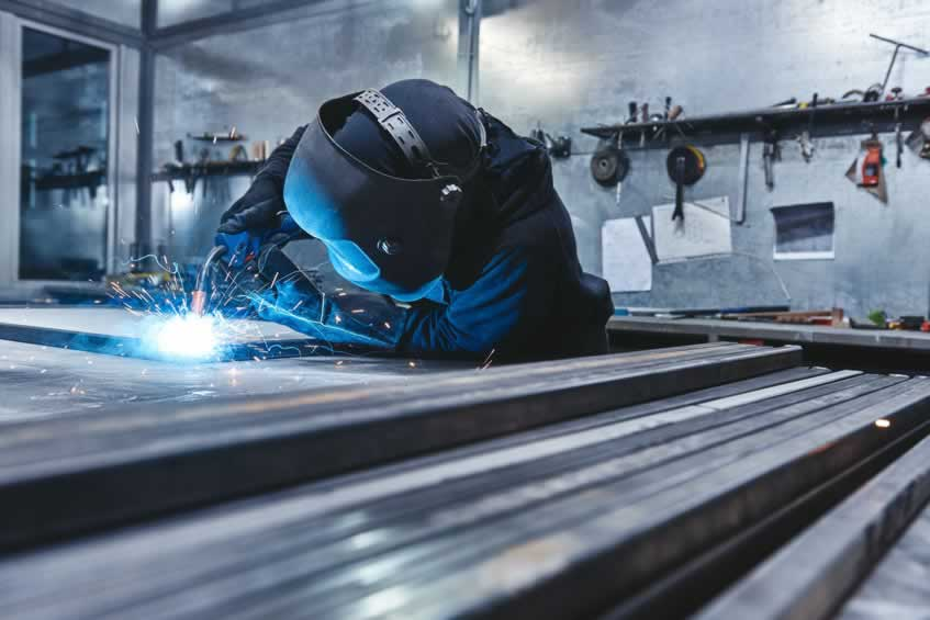 Male worker wearing helmet and gloves welding steel construction at the factory